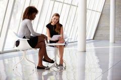 Duas mulheres de negócios que encontram-se na recepção do escritório moderno Foto de Stock Royalty Free
