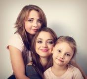 Duas mulheres de sorriso bonitas novas e menina feliz da criança que abraçam a sagacidade imagem de stock