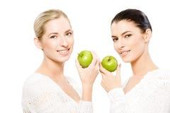 Duas mulheres de sorriso com maçãs fotografia de stock royalty free