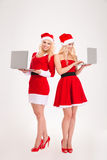 Duas mulheres de sorriso no pano de Santa usando o laptop Imagens de Stock Royalty Free
