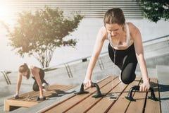 Duas mulheres de sorriso novas, meninas no sportswear que faz exercícios ao escutar a música Exercício, deitando na rua da cidade fotos de stock