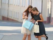 Duas mulheres de sorriso novas que guardam e que olham nos sacos de compras o Fotos de Stock