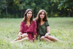 Duas mulheres de sorriso novas que sentam-se na grama Imagens de Stock