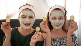 Duas mulheres de sorriso que guardam pepinos Retrato das meninas no salão de beleza dos termas Conceito da beleza da saúde, másca video estoque