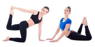 Duas mulheres desportivas bonitas novas que fazem o esticão exercitam o isolador Imagem de Stock Royalty Free