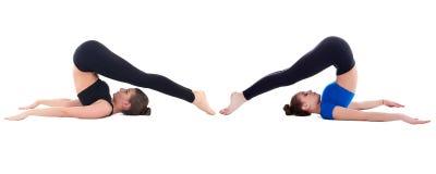 Duas mulheres desportivas bonitas que fazem esticando o exercício isolado sobre Imagens de Stock Royalty Free