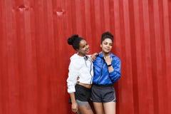 Duas mulheres desportivas que levantam perto da parede vermelha fotos de stock royalty free