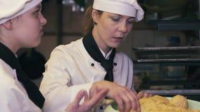 Duas mulheres do cozinheiro que têm o divertimento em uma cozinha video estoque