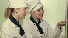 Duas mulheres do cozinheiro que têm o divertimento em uma cozinha vídeos de arquivo