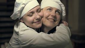 Duas mulheres do cozinheiro que têm o divertimento em uma cozinha filme