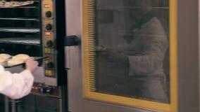 Duas mulheres do cozinheiro que têm o divertimento em uma cozinha padaria video estoque