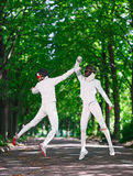 Duas mulheres do esgrimista do florete que lutam sobre a aleia do parque Imagens de Stock