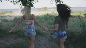 Duas mulheres dos amigos que correm ao longo da estrada na viagem Louro e morena que sorriem e que têm o divertimento em férias s filme