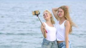 Duas mulheres dos amigos que tomam o selfie com telefone celular perto do rio Duas moças que apreciam perto do rio e que tomam Se vídeos de arquivo