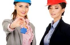 Duas mulheres dos arquitetos com chave da casa Foto de Stock Royalty Free