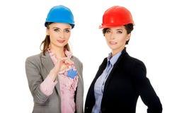 Duas mulheres dos arquitetos com chave da casa Imagens de Stock Royalty Free