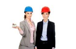 Duas mulheres dos arquitetos com modelo da casa Imagens de Stock Royalty Free