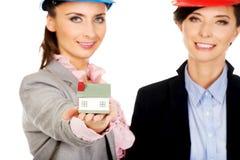 Duas mulheres dos arquitetos com modelo da casa Imagens de Stock