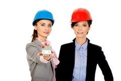 Duas mulheres dos arquitetos com modelo da casa Fotografia de Stock