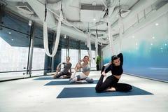 Duas mulheres e homem que trabalham na flexibilidade ao fazer a ioga fotografia de stock royalty free