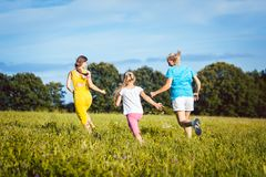 Duas mulheres e menina brincalhão em um prado do verão Fotografia de Stock