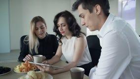 Duas mulheres e o homem têm o vídeo de observação da ruptura de café no portátil filme