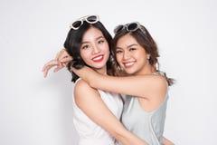 Duas mulheres elegantes nos vestidos agradáveis que estão junto e no havi Fotografia de Stock