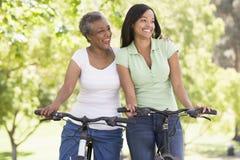 Duas mulheres em bicicletas que sorriem ao ar livre Imagem de Stock