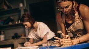 Duas mulheres em uma oficina da cerâmica que faz potenciômetros de argila fotos de stock royalty free