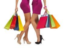 Duas mulheres em vestidos cor-de-rosa com sacos de compras Imagem de Stock