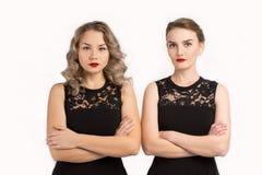 Duas mulheres em vestidos idênticos estão irritadas em se Fotografia de Stock Royalty Free
