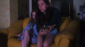 Duas mulheres entram na sala e sentam-se no sofá, tevê do relógio vídeos de arquivo
