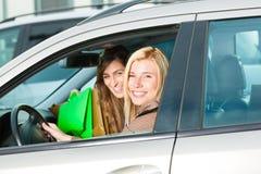 Duas mulheres eram de compra e de condução em casa Imagem de Stock