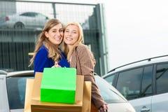 Duas mulheres eram de compra e de condução em casa Imagens de Stock Royalty Free