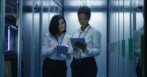Duas mulheres estão trabalhando em um centro de dados com fileiras de cremalheiras do servidor filme