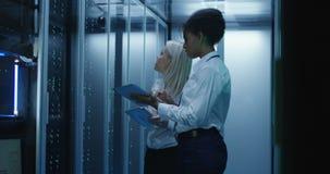 Duas mulheres estão trabalhando em um centro de dados com fileiras de cremalheiras do servidor vídeos de arquivo