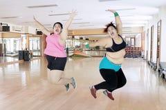 Duas mulheres excessos de peso felizes que saltam junto Imagens de Stock