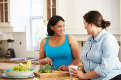 Duas mulheres excessos de peso na dieta que prepara vegetais na cozinha Fotografia de Stock Royalty Free