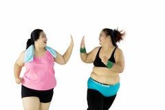 Duas mulheres excessos de peso que dão a elevação cinco Imagem de Stock
