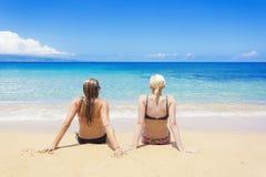 Duas mulheres expõem ao sol bronzear-se em uma praia bonita ensolarada Fotos de Stock Royalty Free