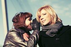 Duas mulheres felizes da forma que teeling os segredos exteriores Foto de Stock Royalty Free