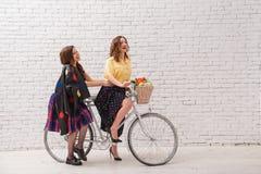 Duas mulheres felizes em vestidos do verão estão montando junto em uma bicicleta retro fotos de stock