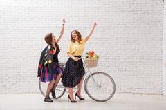 Duas mulheres felizes em vestidos do verão estão montando junto em uma bicicleta retro e nas mãos do gesto para a frente imagens de stock