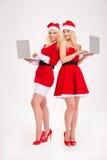 Duas mulheres felizes no pano de Santa usando o laptop Fotografia de Stock Royalty Free