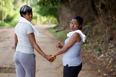 Duas mulheres felizes no sportswear pronto para o exercício na estrada foto de stock royalty free