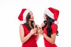 Duas mulheres felizes novas que comemoram no chapéu do Natal bebem o champange no fundo branco imagem de stock