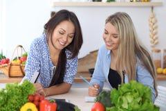 Duas mulheres felizes novas que fazem a compra em linha para fazer o menu pelo tablet pc Amigos que cozinham na cozinha imagem de stock
