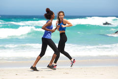 Duas mulheres felizes que correm na praia Imagem de Stock Royalty Free