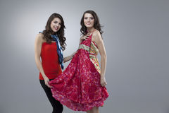 Duas mulheres felizes que tentam o vestido vermelho da flor Fotos de Stock Royalty Free