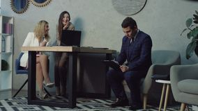 Duas mulheres flertando do escritório que sussurram sobre o colega de trabalho video estoque